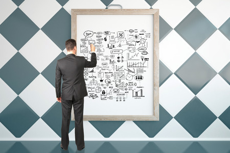 picture frame: Back view of young businessman in suit drawing business sketch in picture frame. Success concept