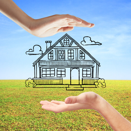 ownerships: Hands holding creative house sketch on beautiful landscape background. Mortgage concept Stock Photo