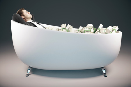lying in: Handsome relaxing businessman lying in bathtub filled with dollar banknotes on grey background. Success concept. 3D Rendering Stock Photo