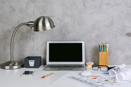 business supplies: Front view of creative workplace with blank laptop display, table lamp, supplies, business sketches and other items on textured concrete wall background. Mock up Stock Photo