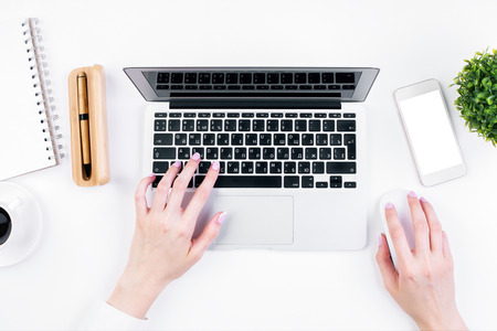 Top view of female hands typing on laptop keypad placed on white office desktop with blank smartphone, coffee cup, decorative plant and supplies. Mock up