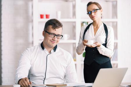 Retrato de joven empresario de éxito en el lugar de trabajo con el secretario servir café