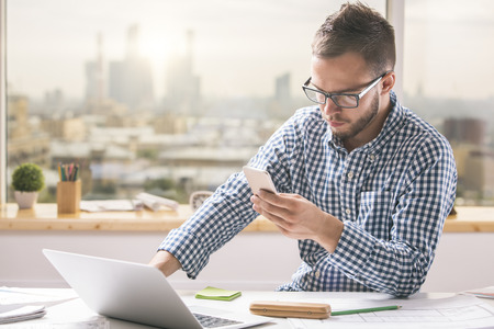 one young man: Portrait of handsome european man using smartphone while sitting at office table with laptop computer and other items