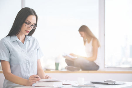 daylight: Two beautiful young women reading in modern bright office with daylight Stock Photo