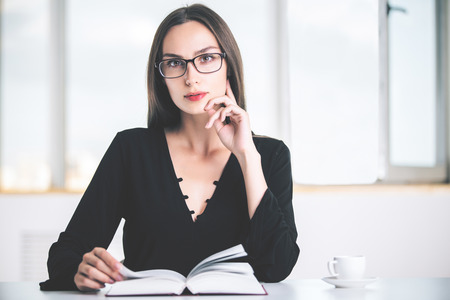 libro abierto: Retrato de la empresaria joven atractiva en camisa elegante negro y gafas sentado en el escritorio blanco con el libro abierto y una taza de café