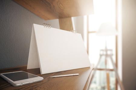 daylight: Closeup of blank calendar stand, smartphone and pen placed on wooden desktop in interior with daylight. Mock up, 3D Rendering Stock Photo