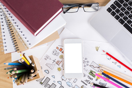 Top view and close up of office workplace with blank white mobile phone, creative business sketches, colorful pencils, notepads, keyboard and other items. Mock up