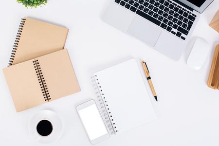 articulos oficina: Vista superior de la tapa blanca de mesa con libretas en blanco, teléfono inteligente, teclado del ordenador portátil, la taza de café y plantas decorativas. Bosquejo