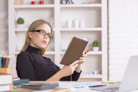 writing paper: Attractive european girl reading notes in diary at modern bright workplace with items on shelves Stock Photo