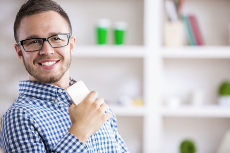 young businessman: Closeup portrait of young european businessman in casual shirt and glasses using mobile phone at workplace