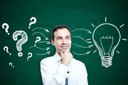 thoughtful: Portrait of thoughtful young businessman standing against chalkboard with creative light bulb sketch. Idea concept