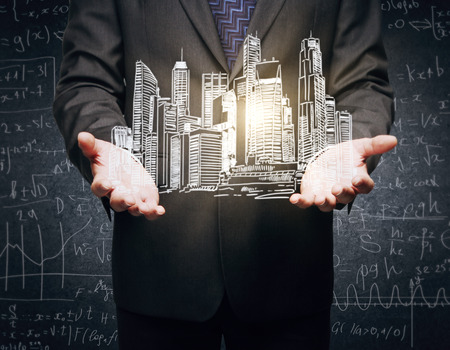 Closeup of businessmans hands holding abstract illuminated city sketch on concrete background with mathematical formulas Stock Photo