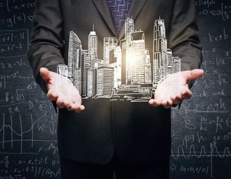 Gros plan des mains d'homme d'affaires tenant un croquis découpé de la ville illuminée sur fond concret avec des formules mathématiques Banque d'images