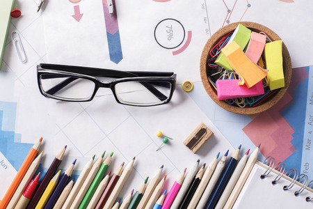 office supplies: Top view of messy office workplace with colorful supplies, financial reports and glasses