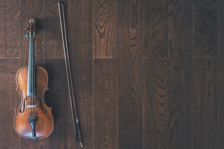 cellos: Top view of violin with bow on dark wooden floor with copy space
