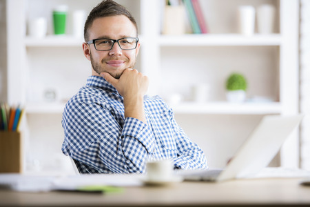 Portrait of thoughtful smiling man in casual shirt and glasses sitting at desk with laptop and other items in modern office Stock Photo