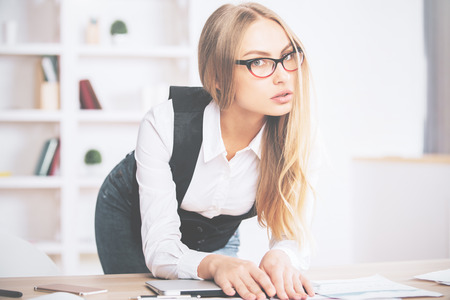 attractive woman: Portrait of attractive young woman leaning on office desk with laptop and paperwork