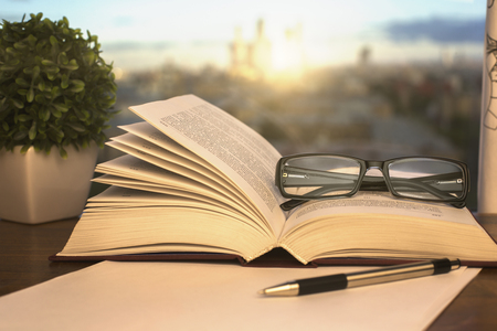 notepaper: Closeup of open book, glasses, paper sheet, pen and decorative plant on blurry background with city view and sunlight Stock Photo
