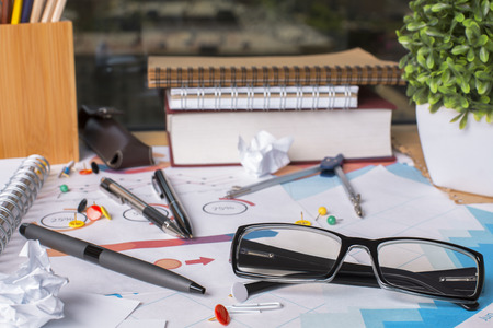 ball pens stationery: Closeup of messy office desktop with glasses, supplies, financial reports and other items