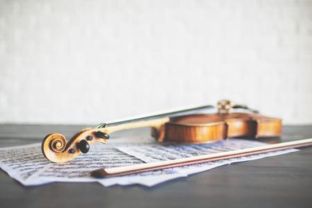 明るい背景にバイオリン、弓、音楽シートの側面図です。コンサートのコンセプト