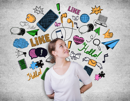 creative communication: Attractive young woman on concrete background with creative communication icons drawings. Social media concept Stock Photo