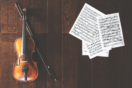 a rehearsal: Violin, bow and music sheets placed vertically on wooden floor. Concert rehearsal concept Stock Photo