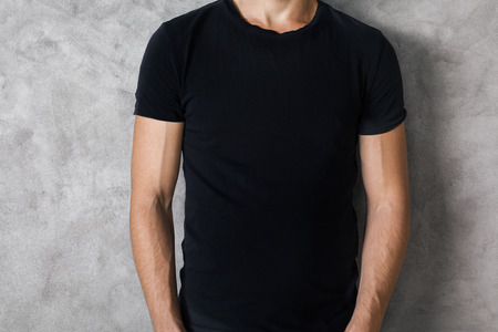 a shirt: Closeup of young guys body in empty black t-shirt on textured concrete wall background. Mock up