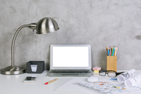 business supplies: Front view of creative workplace with blank white laptop display, table lamp, supplies, business sketches and other items on textured concrete wall background. Mock up Stock Photo