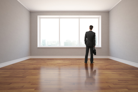 shiny floor: Back view of young businessman standing in unfurnished interior with shiny wooden floor, grey walls and window with city view. 3D Rendering