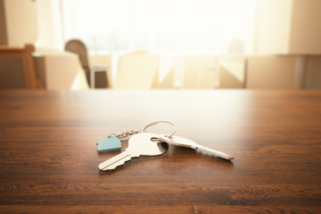 Closeup of keys with house keychain on wooden table in blurry interior. Real estate and mortgage concept. 3D Rendering