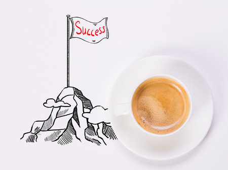 close: Top view of white desktop with coffee cup and creative drawing of mountain top with flag. Success concept