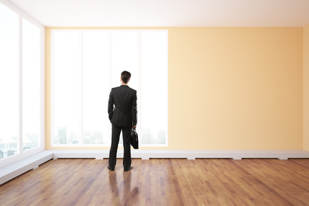 front: Back view of young businessperson with briefcase standing in unfurnished interior with wooden floor and panoramic windows with city view. 3D Rendering Stock Photo