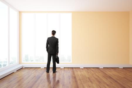 finestra: Vista posteriore di giovane uomo d'affari con la valigetta in piedi in interni non arredato con pavimento in legno e finestre panoramiche con vista sulla città. Rendering 3D