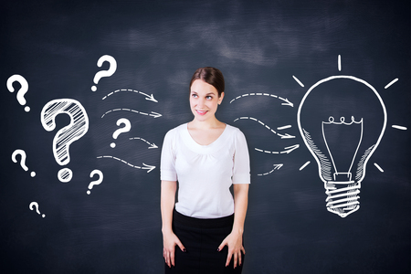 idea sketch: Attractive young female on chalkboard background with creative light bulb and question marks sketch. Idea concept