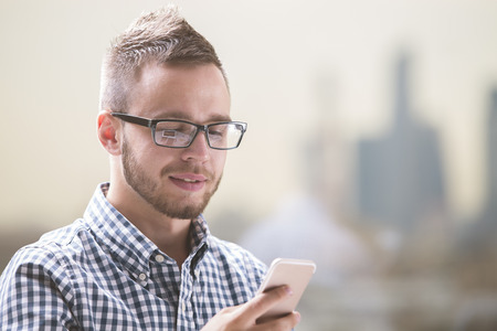 Closeup portrait of young european businessman in casual shirt and glasses using cellular phone at workplace Stock Photo