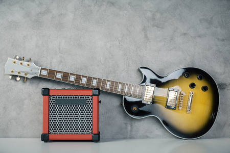 guitar amplifier: Electric sunburst guitar and amplifier on concrete background