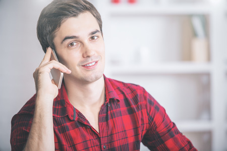 Portrait of attractive young man in casual red shirt talking on cellular phone