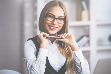specs: Portrait of smiling european female with smartphone in hand, wearing formal outfit and glasses