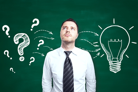 Handsome young male thinking on chalkboard background with creative light bulb and question marks sketch. Idea concept
