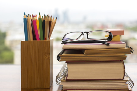 lapiz: Pile of books and notepads, glasses, stickers and pencils in wooden box on blurry background. Education concept
