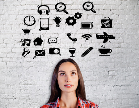 attractive woman: Portrait of attractive young woman with social media icons on white brick background Stock Photo