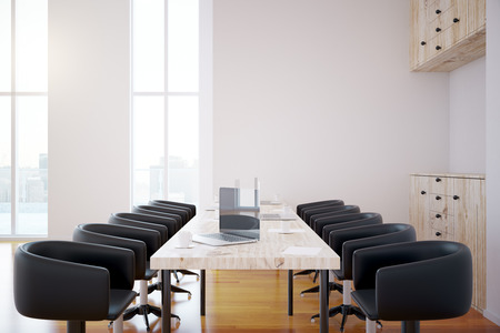 work area: Side view of modern interior with laptops on table, seats, cupboard and windows with city view. 3D Rendering Stock Photo