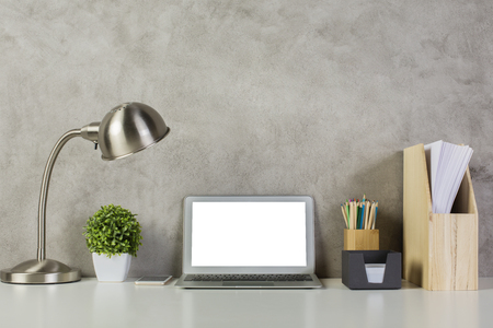 portables: Blank white computer on desktop with table lamp, decoratve plant, wooden folder with documents and supplies on concrete wall background. Mock up