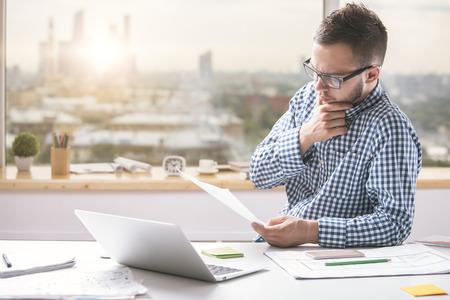 Portret van aantrekkelijke jonge man die papierwerk in modern kantoor doet. Knappe kantoormeester die documenten op de werkplek behandelt