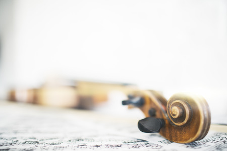 Closeup of violin and music sheets on bright background Stock Photo