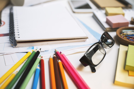 Closeup of office workplace with glasses, colorful supplies and blank spiral notepad Stock Photo