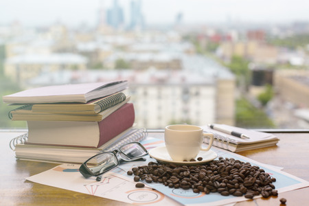 Wooden window stool with coffee beans, cup, glasses, financial report and books on blurry city background