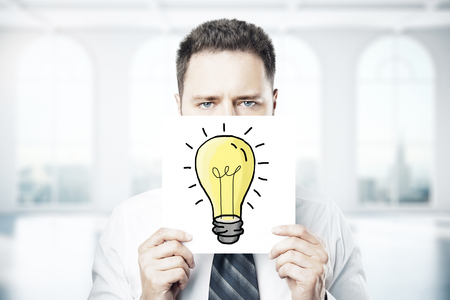 covering: Businessman covering face with light bulb drawn on paper sheet. Idea concept Stock Photo
