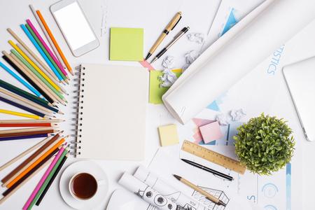 planta de cafe: Vista superior del escritorio creativo con la libreta espiral en blanco, smartphone blanco, taza de café, planta decorativa, informe financiero y fuentes coloridas. Bosquejo Foto de archivo