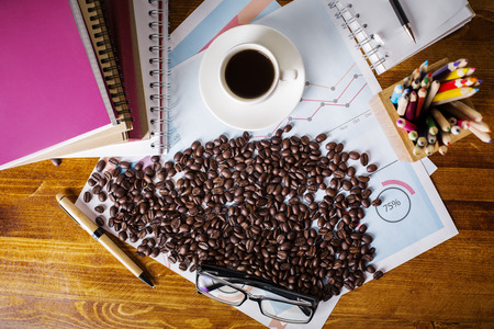 Top view of wooden desktop with coffee beans, cup, colorful supplies, financial report and other items